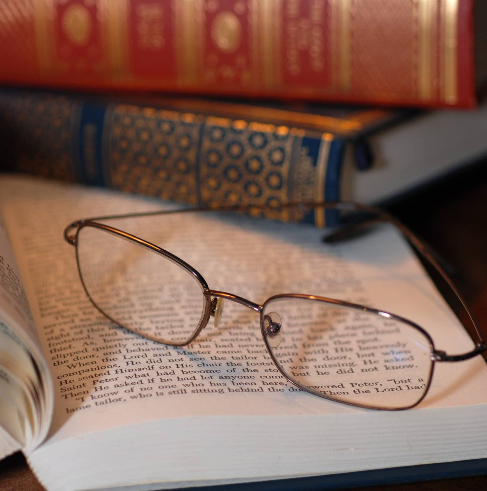 Eyeglasses resting on stack of academic books on desk