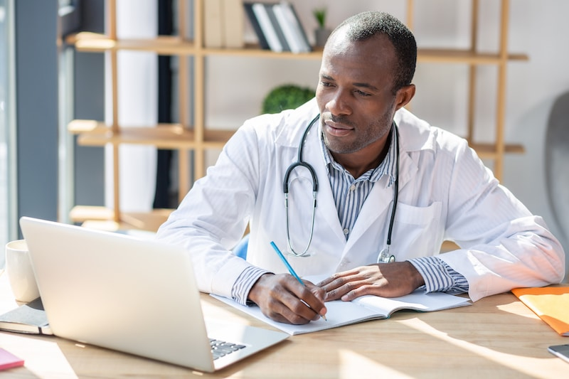 Black male physician with stethoscope conducting research makes notes with pen while looking at laptop
