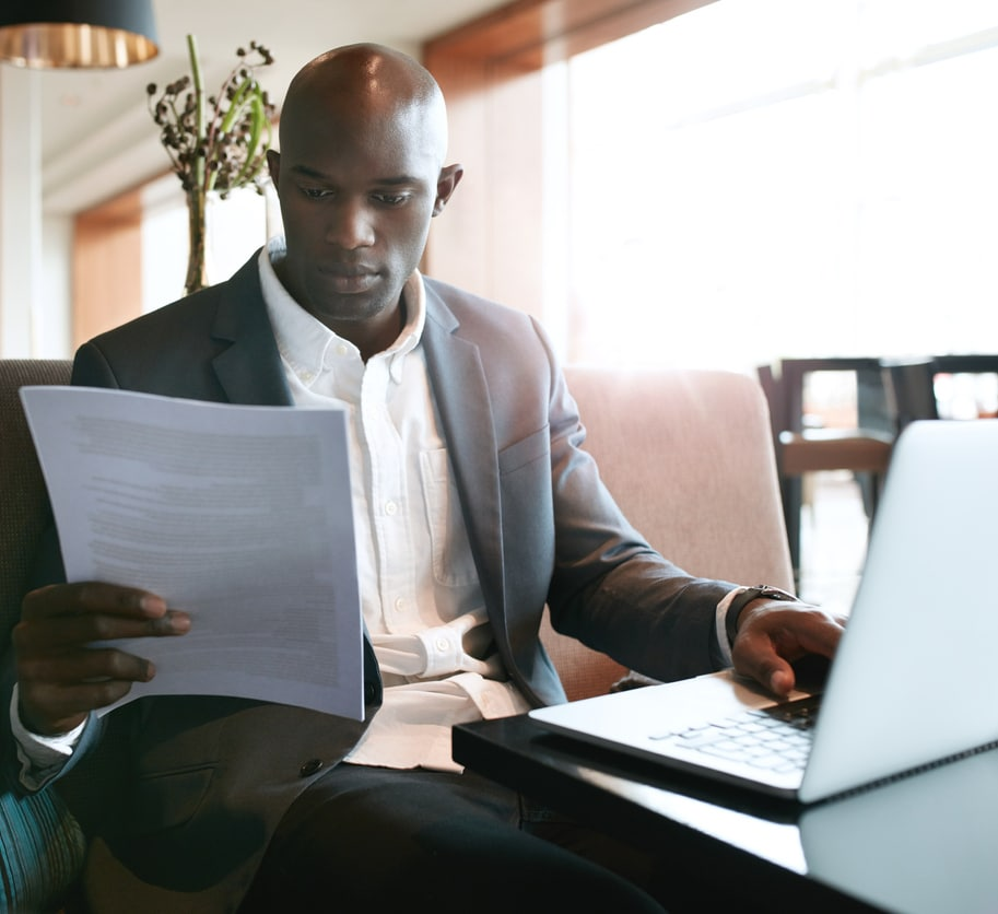 Black male college dean with laptop reviews paper during faculty annual review